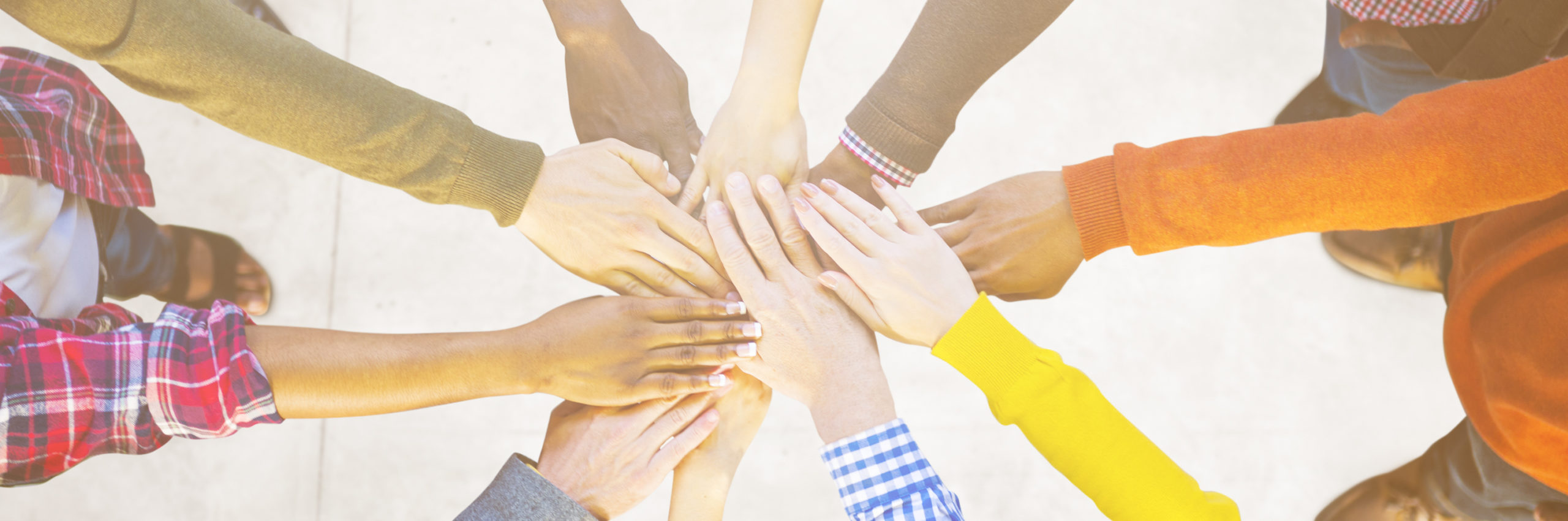 Group of people putting hands together in a circle
