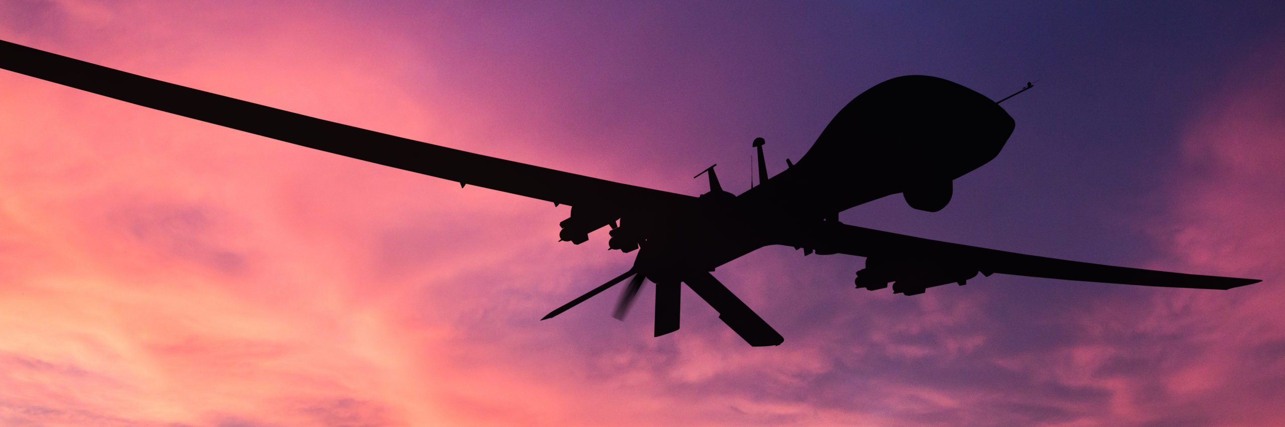 Military drone silhouette on sunset background. - Image [shutterstock]