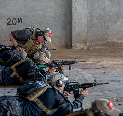 An instructor (top) with the Diplomatic Security Service's Antiterrorism Assistance (ATA) program coaches law enforcement officers with a SPEAR team from Tunisia during the weapons test at the first SPEAR Quick Response Force Summit Challenge, December 10, 2018, in Nairobi. ATA trains Special Program for Embassy Augmentation and Response teams in participating nations to respond within minutes to emergencies involving U.S. diplomatic facilities or personnel. (51 Seconds photo)