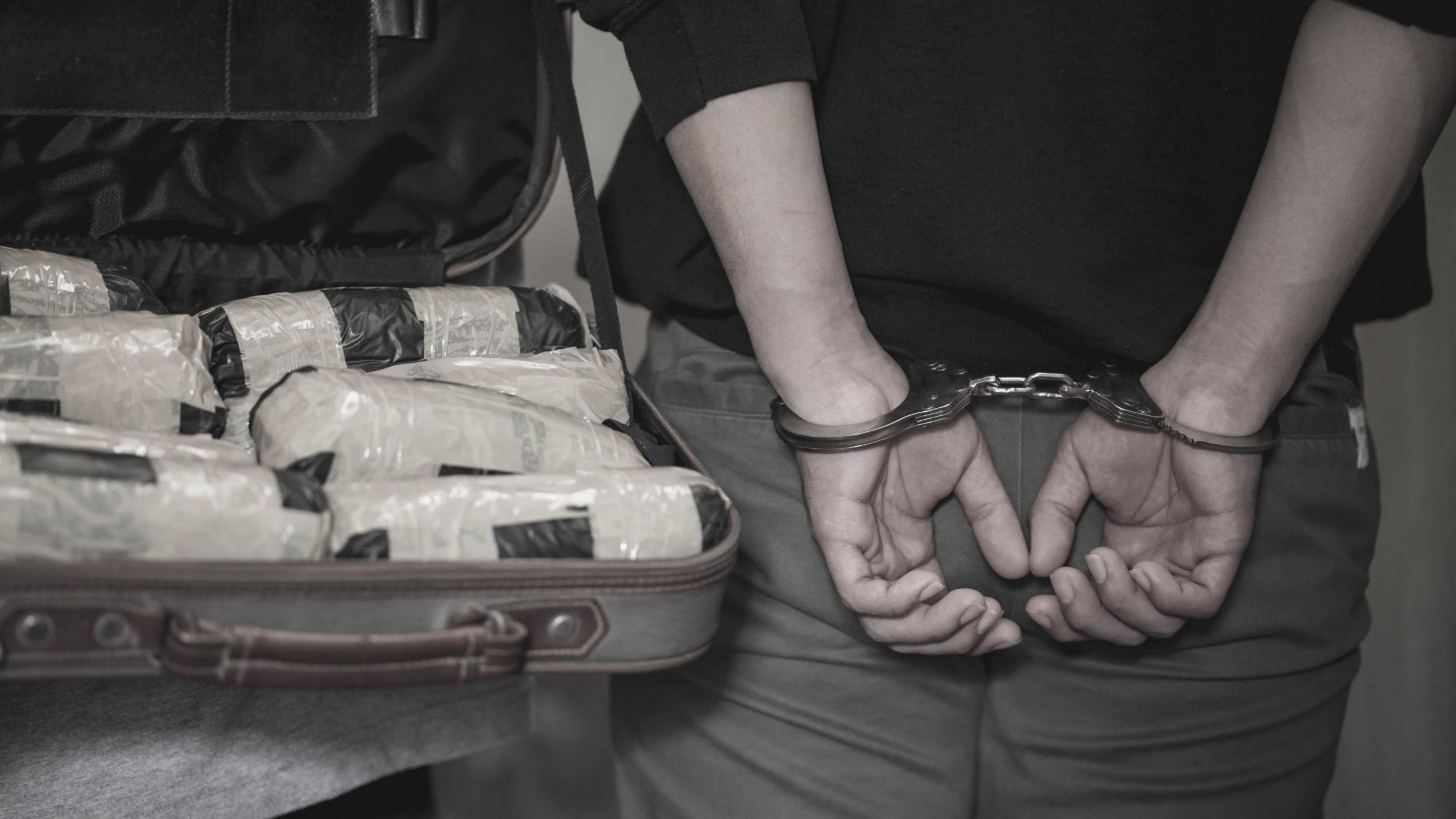 Police arrest drug trafficker with handcuffs. [Shutterstock]