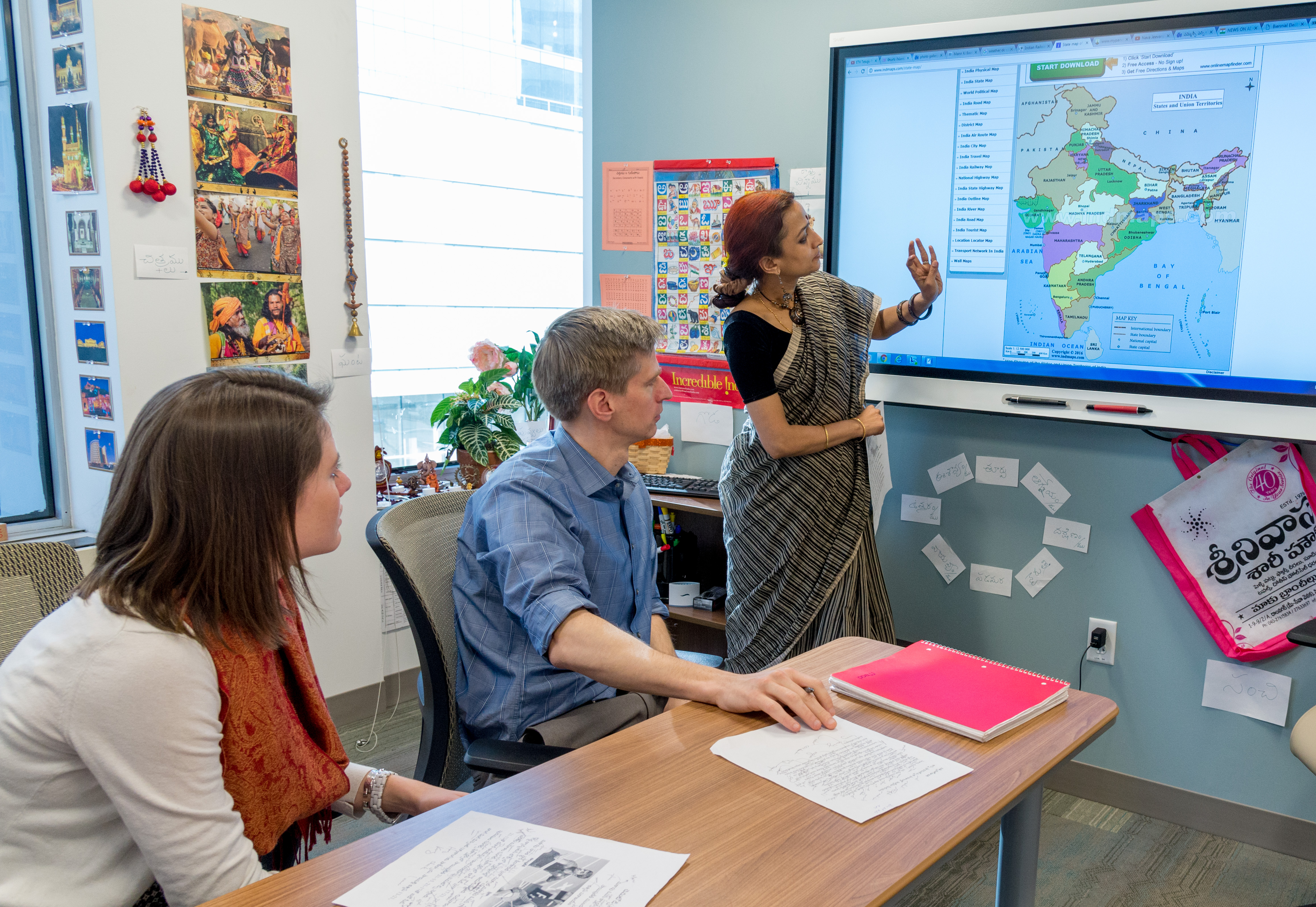 FSI students studying in a foreign language classroom. The instructor is motioning to the electronic screen.