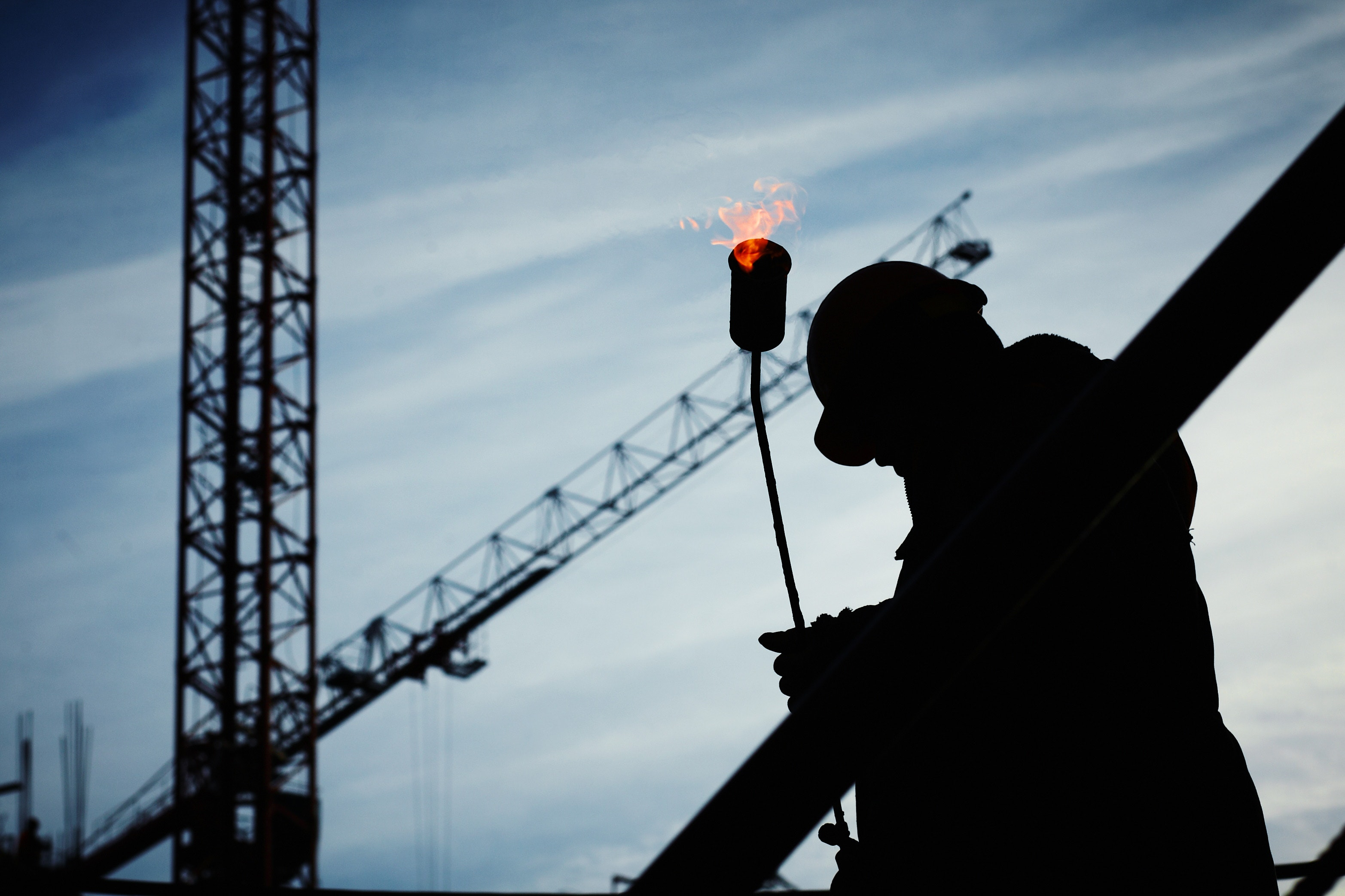 Silhouette of a man holding welding equipment at a construction site. (Yury Kim, 2008)
