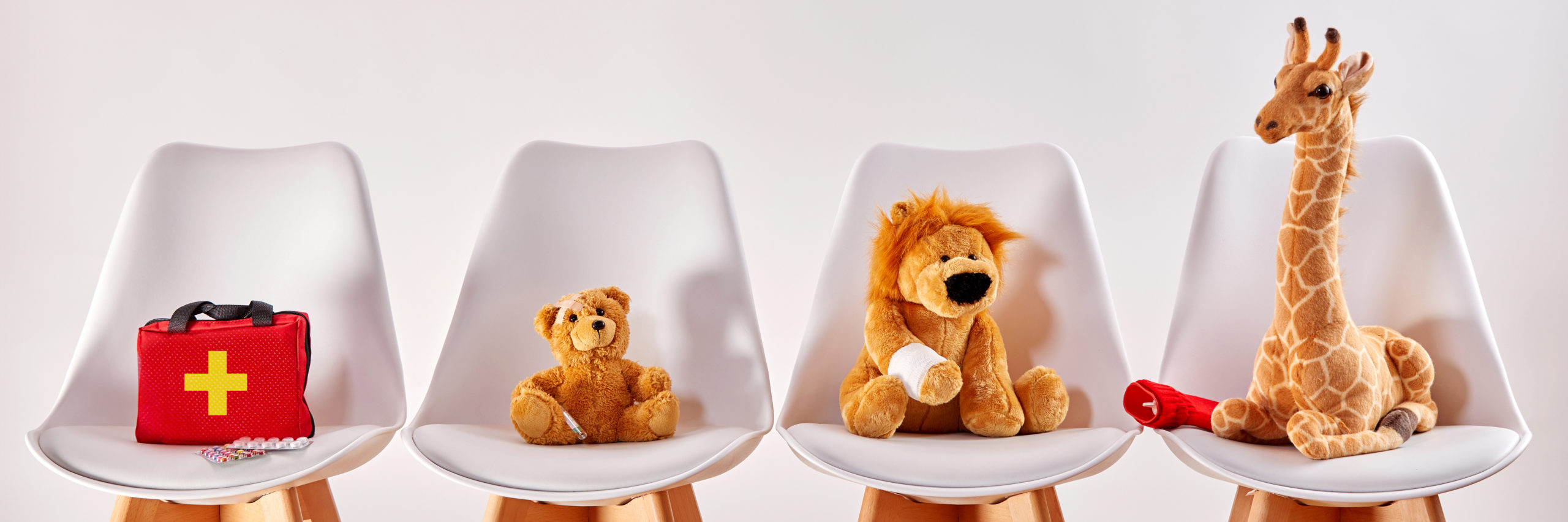 Three cute stuffed animal toys on chairs in the waiting room of a modern hospital or health center for children - Image