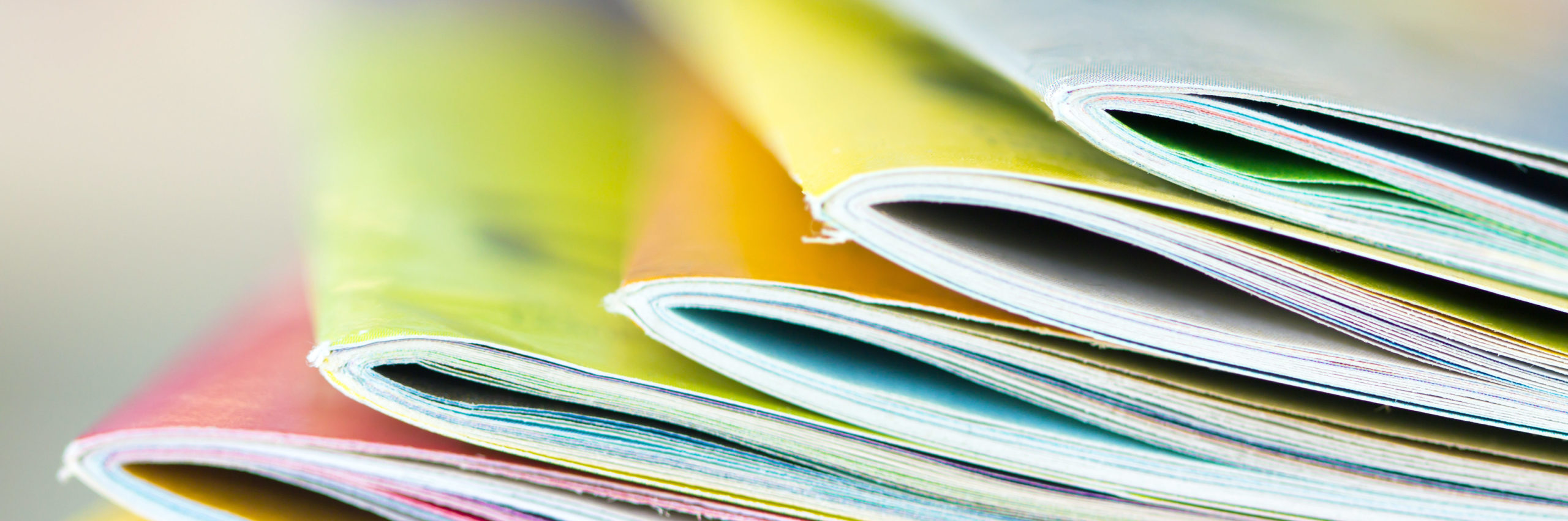 Close up edge of colorful magazine stacking with blurry bookshelf background for publication and publishing concept , extremely DOF - Image