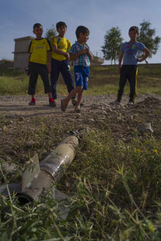 Children with a piece of unexploded ordnance they found while playing in northern Iraq. (Photo courtesy of MAG)