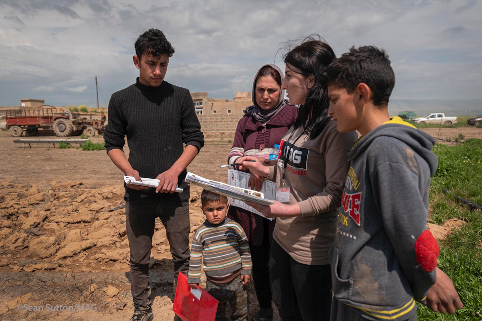 U.S.-funded Mines Advisory Group (MAG) staff talks with a family in Til Azir village. The family contacted MAG after identifying wires and IED components near their home in an area liberated from ISIS. (Photo courtesy of MAG)