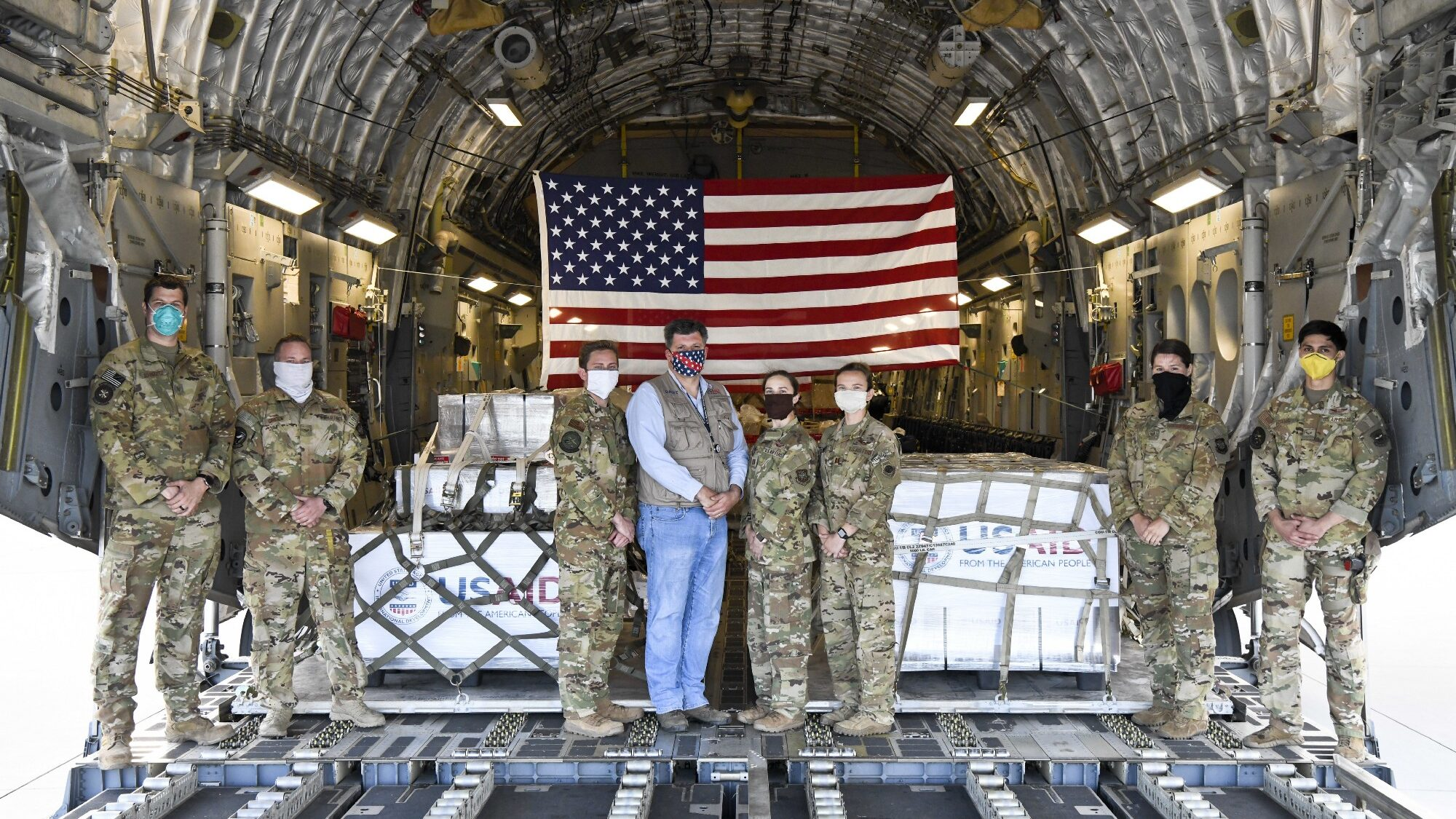 U.S. Air Force aircrew and USAID Assistant Administrator Brock Bierman in front of ventilators on their way Moscow in May as part of the U.S. Government's global response to the coronavirus pandemic. / Christopher Quail, U.S. Air Force