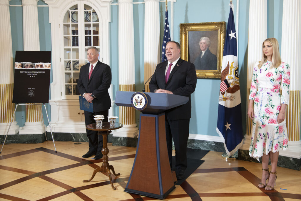 Secretary Pompeo stands with Ambassador John Cotton Richmond and Advisor Ivanka Trump in a room presenting the TIP Report release.