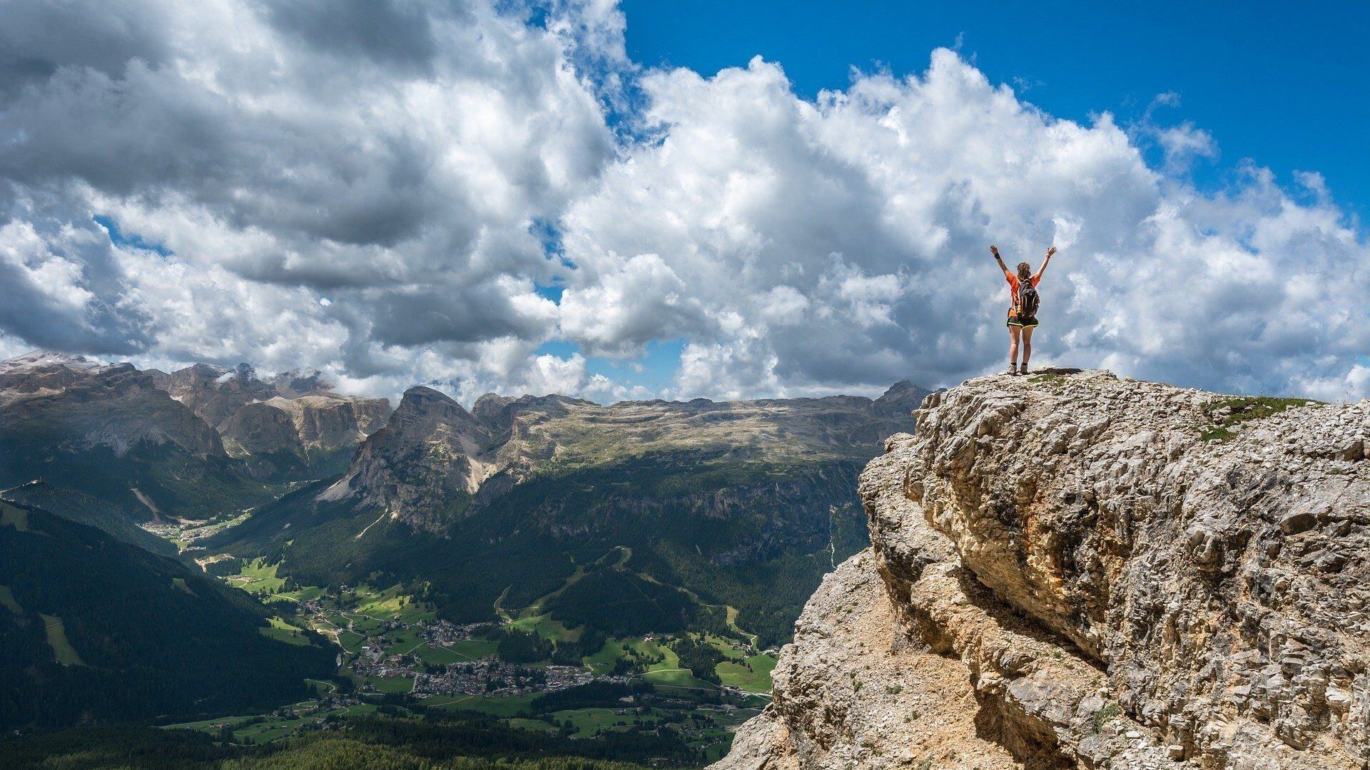 Woman in hiking gear, standing atop a mountain looking over a valley.