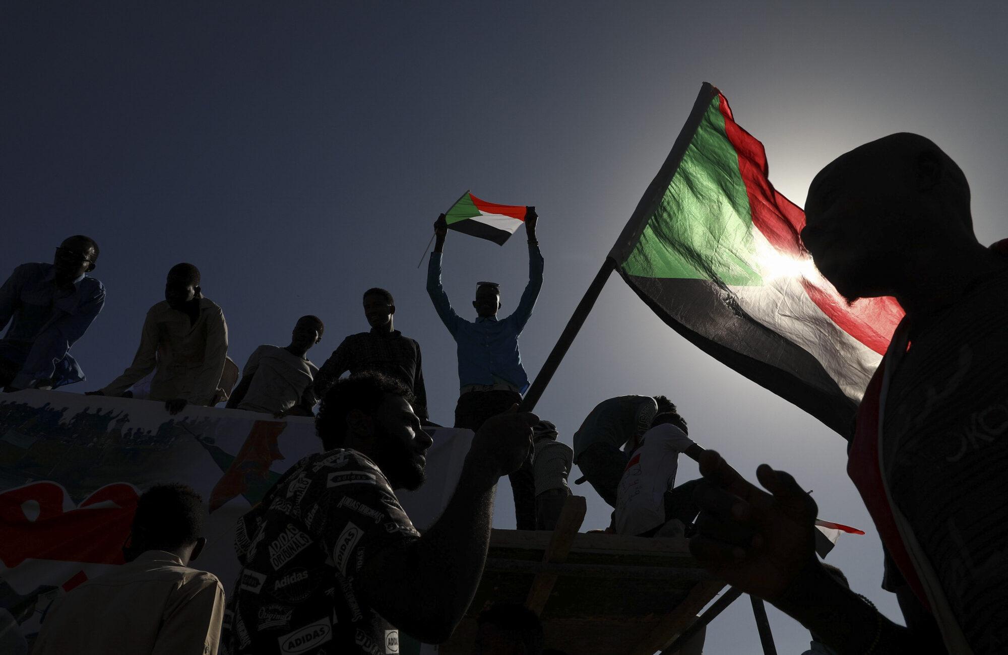 Sudanese men holding flags. [AP Image]