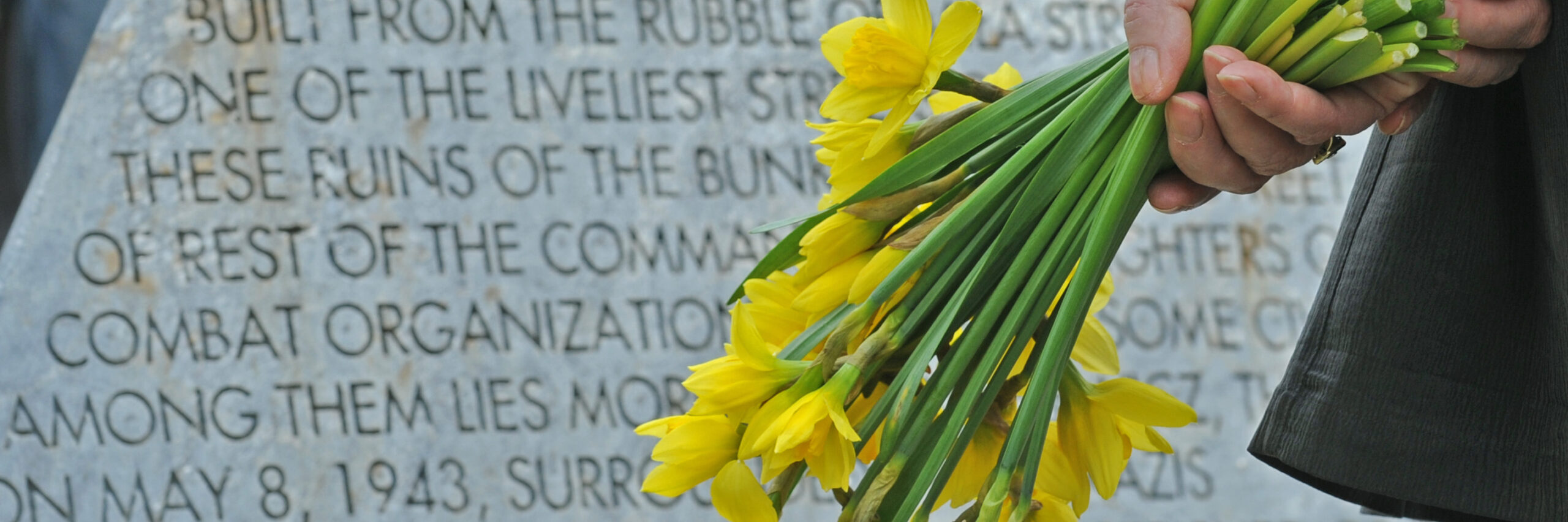 A woman stands with flowers in front of a memorial stone during a ceremony marking the 71st anniversary of the beginning of the Warsaw Ghetto Uprising, in Warsaw, Poland, Saturday, April 19, 2014. Some 200 members of the Jewish community and Warsaw residents have observed the ceremony of the city ghetto's ill-fated uprising against German Nazi forces. (AP Photo/Alik Keplicz)