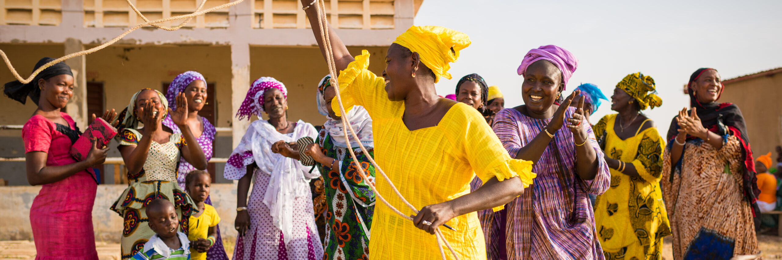 """Ms. Khady Ndongo (in purple) is a community nutrition volunteer in the Matam region of Senegal. Here she has organized a """"Passing on the Gift"""" ceremony between women in her village and those in a village 7 kilometers away and has presented two goats to a member of a Debbo Galle (competent mothers) Group. Through this process, families that receive livestock through the Feed the Future Senegal Yaajeende project, implemented by a consortium led by NCBA CLUSA, pass on offspring to other targeted families in their community. This allows recipients of a productive asset to assist others as they have been helped and to share resources, thereby encouraging resilience across the community. *Passing on the Gift is a trademark of Heifer International, a Feed the Future Yaajeende consortium partner. Photo by Clement Tardif, Feed the Future Senegal - Yaajeende"""