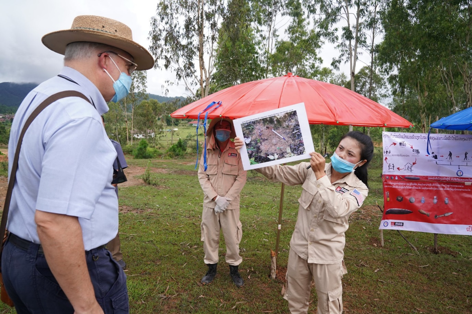 A Mines Advisory Group survey team member briefs Ambassador Haymond on a cluster sub-munition found in Latngon village, Xieng Khouang Province, in Lao PDR. (Photo courtesy of U.S. Embassy Vientiane)