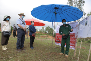 A MAG survey team leader briefs Ambassador Haymond on the current task. (Photo courtesy of U.S. Embassy Vientiane)