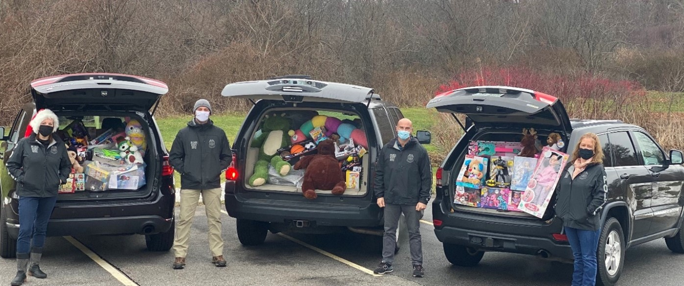 Diplomatic Security Service (DSS) special agents and investigative assistants stand by cars loaded with toys bound for the Unites States Marine Corps (USMC) Toys for Tots program, Portsmouth, NH, December 2020. (U.S. Department of State photo)