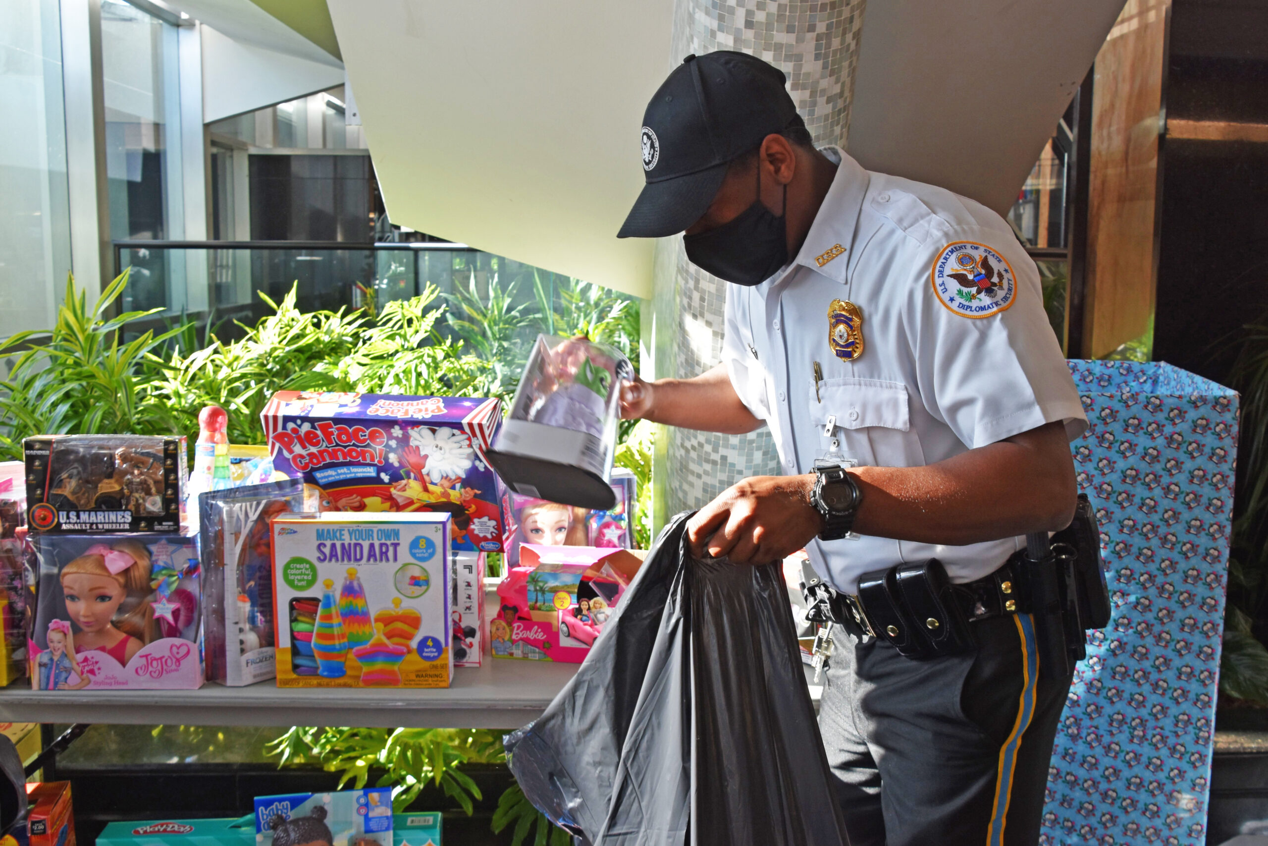 A DSS uniformed guard packs toys collected from Department of State employees and provided to the USMC Toys for Tots program, December 17, 2020. (U.S. Department of State photo)
