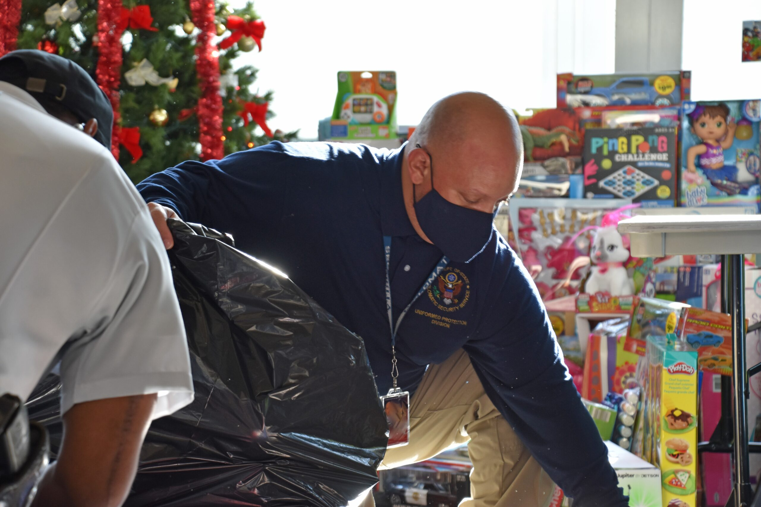 A DSS security officer packs toys collected from Department of State employees and provided to the USMC Toys for Tots program, December 17, 2020. (U.S. Department of State photo)