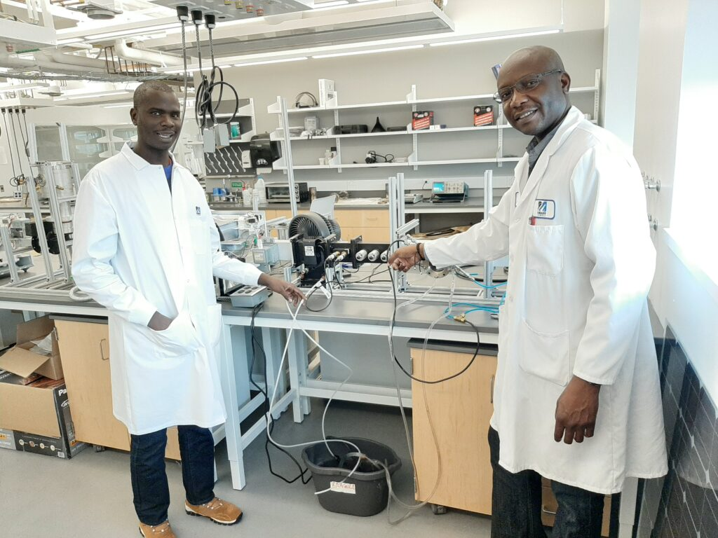 Benard Tabu (Left), 2019 Fulbright Student from Uganda, and Dassou Nagassou, 2013 Fulbright Student from Chad and current Post-Doctoral researcher, pose near a Microwave Plasma Reactor for the decomposition of carbon-dioxide into valuable products, University of Massachusetts, Lowell, November, 2019. (Photo courtesy of Benard Tabu)